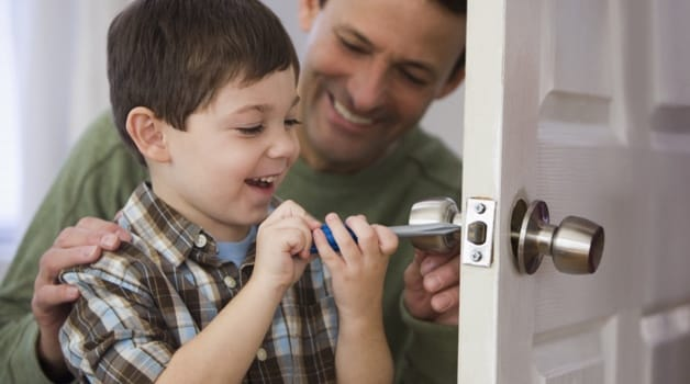 Father and son unlocking door